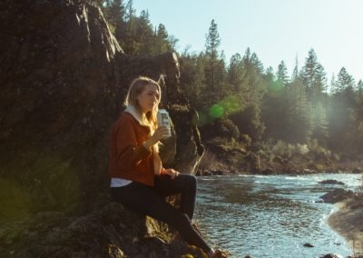 woman in blue long sleeve shirt sitting on rock near river during daytime